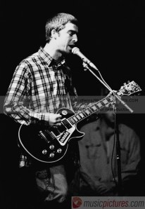 Noel Gallagher performing with his Les Paul Custom with sticker